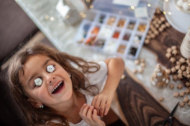 巻き毛のかわいい女の子は、ボタン、毛糸、フェアリーライトで紙の円錐形のクリスマスツリーを手作りして飾っています。