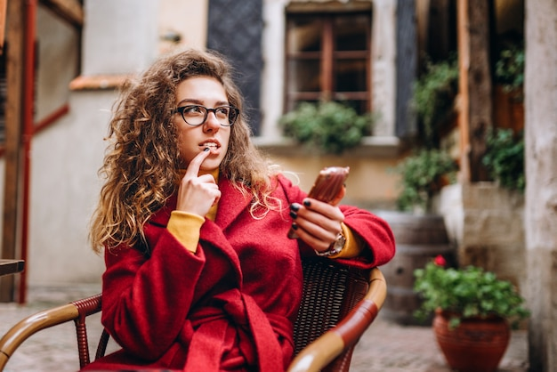 Cute girl with curly hair using phone outdoor
