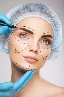 Милая девушка с темными бровями в синей медицинской шляпе на фоне студии, руки врача в синих перчатках, рисуя линии перфорации на лице, концепция пластической хирургии.