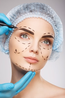 Милая девушка с темными бровями в синей медицинской шляпе у стены, руки врача в синих перчатках, рисуя линии перфорации на лице, концепция пластической хирургии.