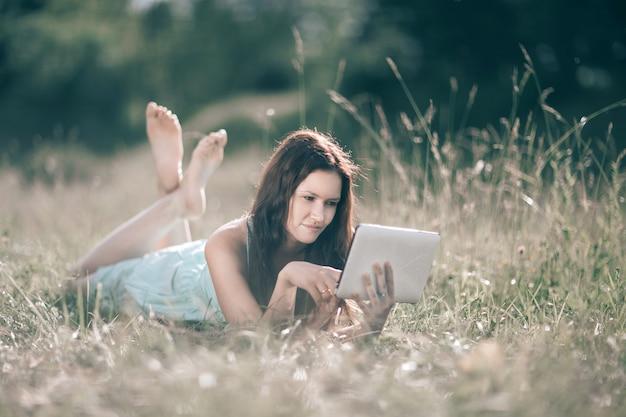 여름날 잔디밭에 누워 디지털 태블릿을 가진 귀여운 소녀. 사람과 기술