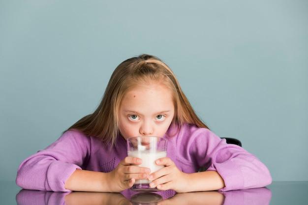우유를 마시는 다운 증후군을 가진 귀여운 소녀