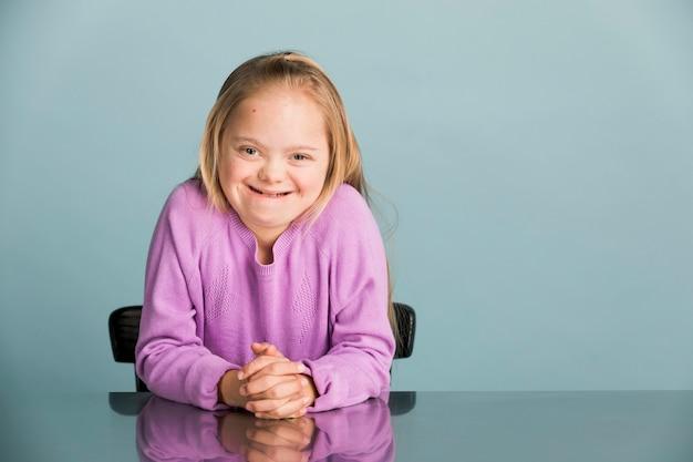보라색 스웨터를 입은 다운 증후군을 가진 귀여운 소녀