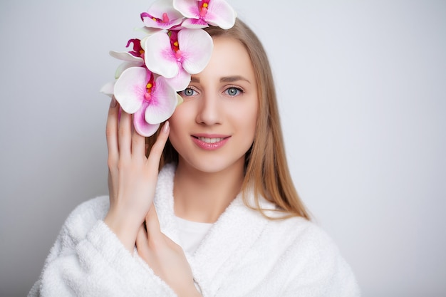 Cute girl with flowers after taking a shower