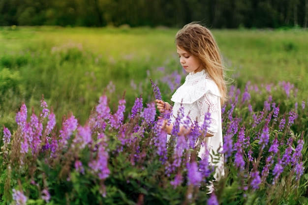 Cute girl with flowers in summer