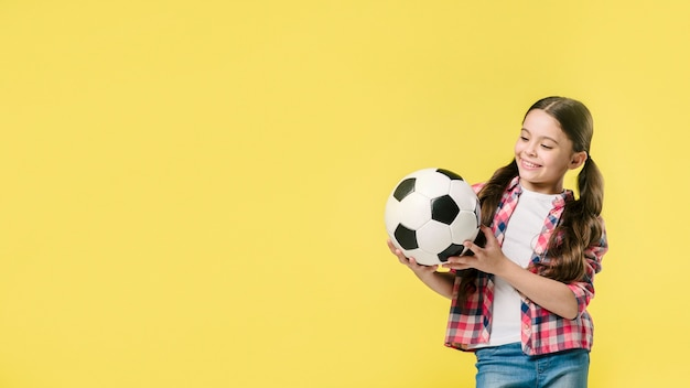 Cute girl with football in studio
