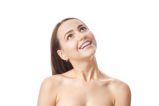 Cute girl with fresh skin and white teeth heads up and looking amased at the top