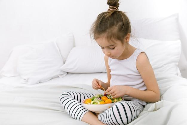 Милая девушка с фруктами и овощами на белой кровати