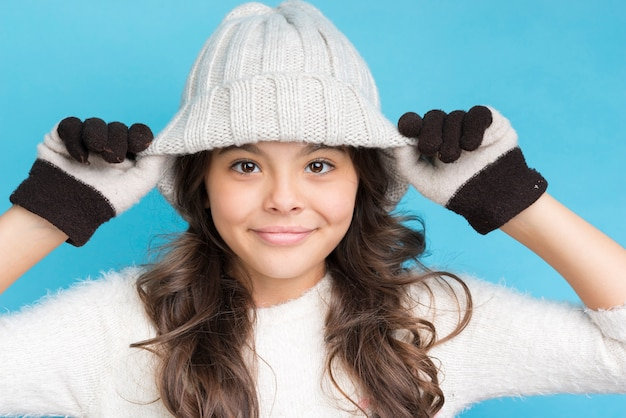 Cute girl with gloves and hat on head