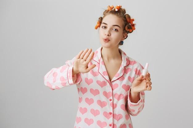 Ragazza carina con bigodini in capelli e pigiama, unghie polacche