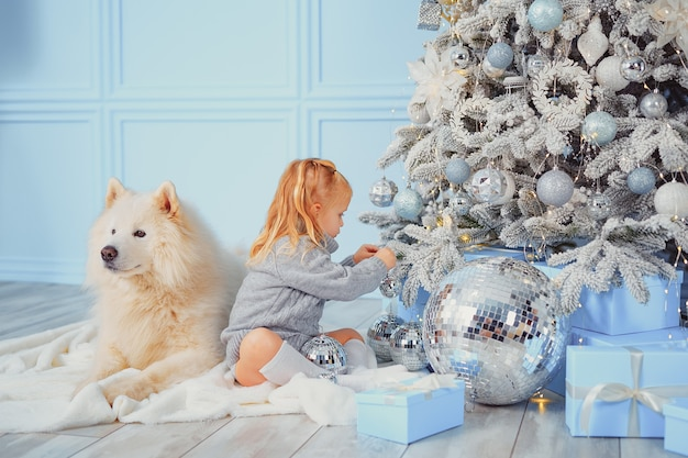 Cute girl with her dog decorating christmas tree at home.