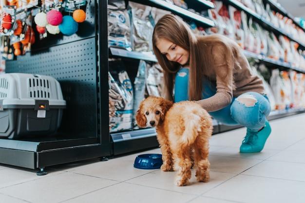애완 동물 가게에서 그녀의 푸들 강아지와 함께 귀여운 소녀.