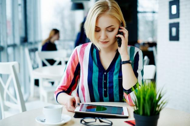 태블릿, 휴대 전화 및 커피, 초상화, 프리랜서 개념, 온라인 쇼핑의 컵 카페에 앉아 화려한 셔츠를 입고 가벼운 머리를 가진 귀여운 소녀.