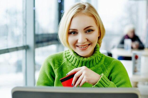 노트북 및 신용 카드, 초상화, 프리랜서 개념, 온라인 쇼핑 카페에 앉아 녹색 스웨터를 입고 가벼운 머리를 가진 귀여운 소녀.