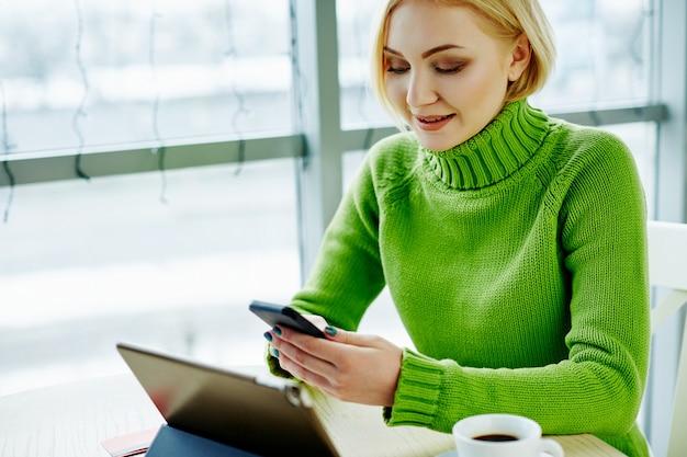 태블릿, 휴대 전화 및 커피, 초상화, 프리랜서 개념, 온라인 쇼핑의 컵 카페에 앉아 녹색 스웨터를 입고 가벼운 머리를 가진 귀여운 소녀.