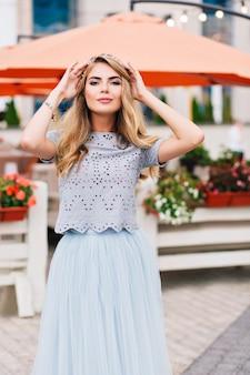 青いチュールスカートに長いブロンドの髪のかわいい女の子がテラスの背景を歩いています。