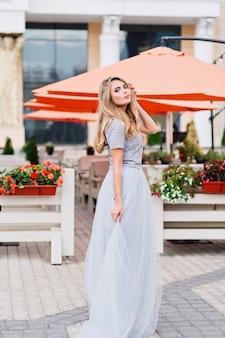 Ragazza carina con lunghi capelli biondi in gonna lunga in tulle blu sta camminando sulla strada.