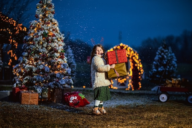 Cute girl with long curly hair in beige coat holding big presents against christmas decorations. copy space.