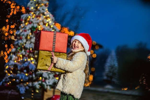 Cute girl with long curly hair in beige coat and santa's cap holding big presents against christmas decorations. copy space.