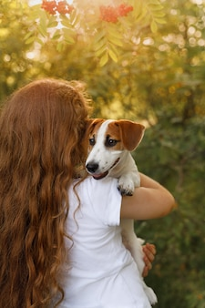 Cute girl with long curly hair embraces the puppy with a view from behind.