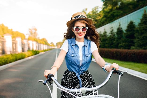 道路上のカメラに自転車を運転するサングラスで長い巻き毛を持つかわいい女の子。彼女はロングスカート、ジャーキン、帽子をかぶっている。彼女は幸せそうです。