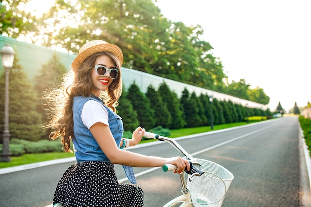 Cute girl with long curly hair in sunglasses is going by bicycle  on road. she wears long skirt, jerkin, hat. she looks happy in sunshine.