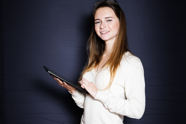 Cute girl with long hair holds a tablet in her hands and looks at the camera