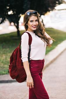 Милая девушка с длинными волосами улыбается в городском парке. на ее вещах есть цвет марсала. она выглядит довольной.