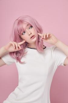 ピンクのロングヘア、ヘアカラーのかわいい女の子。ピンクの背景に白いドレスを着た美しい女性。色の髪、完璧な髪型
