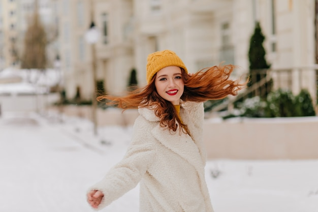 雪の上で踊る長いウェーブのかかった髪のかわいい女の子。冬に楽しんでいるコートの楽しい女性モデル。