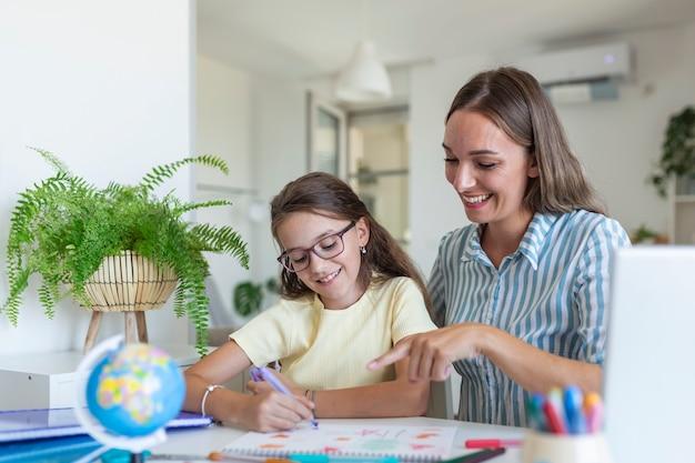 Милая девушка с матерью дома делать домашнее задание. мать помогает маленькой дочке делать уроки для школы. концепция образования и семьи