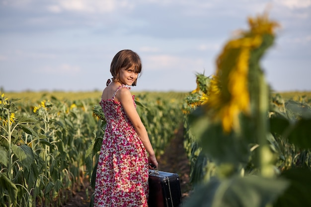 Cute girl with old suitcase in a sunflower field.