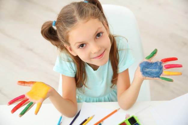 집에서 페인트에 손바닥과 귀여운 소녀
