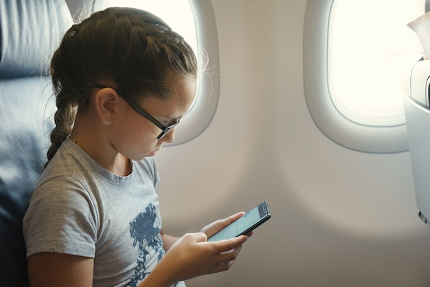 Cute girl with a pigtail sits in a chair by the window in the cabin of the aircraft and communicates in social networks on a smartphone.