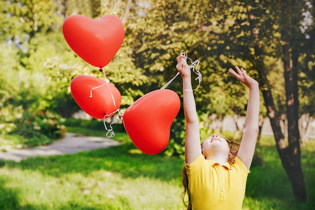 Cute girl with red balloons on outdoors.