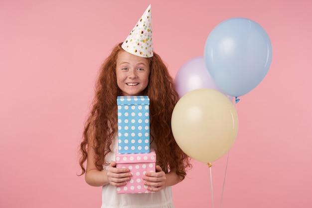Ragazza carina con capelli ricci rossi in abito bianco e berretto di compleanno felicemente guardando a porte chiuse con scatole regalo nelle mani, in piedi su sfondo rosa con ampio sorriso, esprime vere emozioni positive
