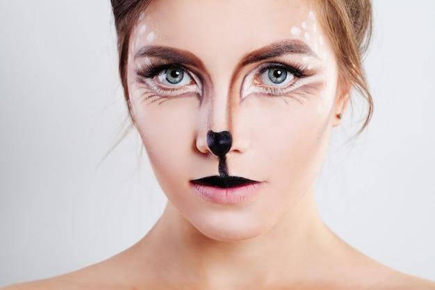 Милая девушка с макияжем оленей животных. лицо крупным планом