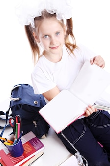 Cute girl with schoolbag sitting on the desk