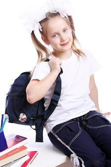 Милая девушка с школьным портфелем сидит на столе