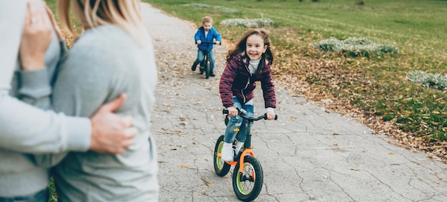 Cute girl with small brother riding the bike in the park while parents are watching them