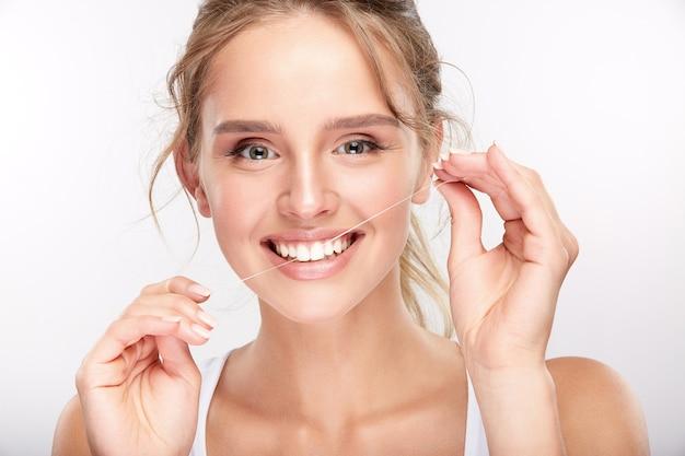 白いスタジオの背景に真っ白な歯を持つかわいい女の子、歯科のコンセプト、完璧な笑顔、カメラを見て、クローズアップ、デンタルフロスを使用して。