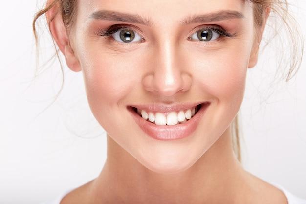 Милая девушка с белоснежными зубами на белом фоне студии, концепция стоматологии, идеальная улыбка, глядя на камеру, крупным планом.