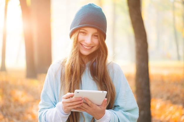 秋の公園でタブレットとかわいい女の子
