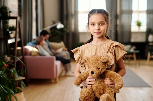 Милая девушка с игрушечным медведем стоит в гостиной против своей семьи