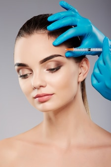 Cute girl with thick eyebrows at studio background, doctor's hands wearing blue gloves near patient's face, holding syringe with botex near face, looking down.