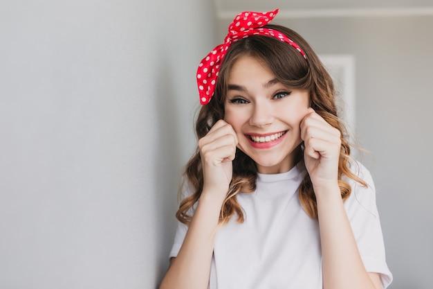 トレンディな髪型のかわいい女の子が浮気します。変な顔をしている美しいインスピレーションを得た女性の屋内ショット。