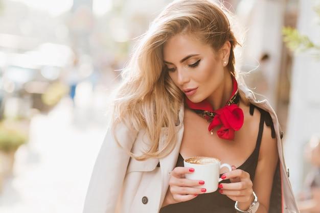 晴れた日にリラックスして目を閉じてラテを飲むトレンディなメイクのかわいい女の子。一杯のコーヒーとコートでポーズをとるブロンドの髪を持つゴージャスな日焼けした女性の屋外の肖像画。