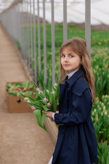 튤립 성장 온실에서 금발 머리 봄 튤립과 귀여운 소녀