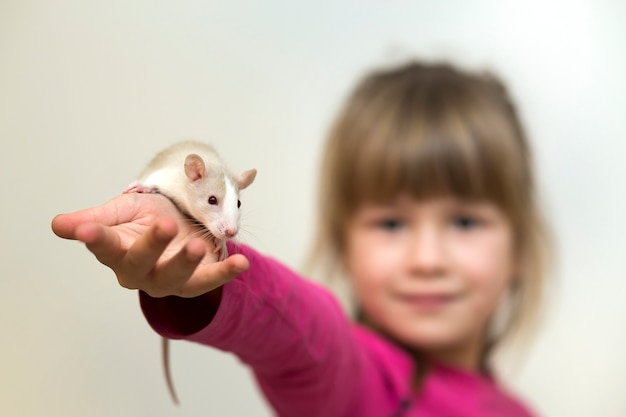 Cute girl with white pet mouse on her hand