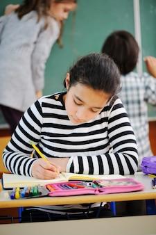 Cute girl writing in school classroom